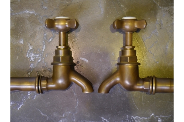 Weathered brass finish on a pair of bib taps.
