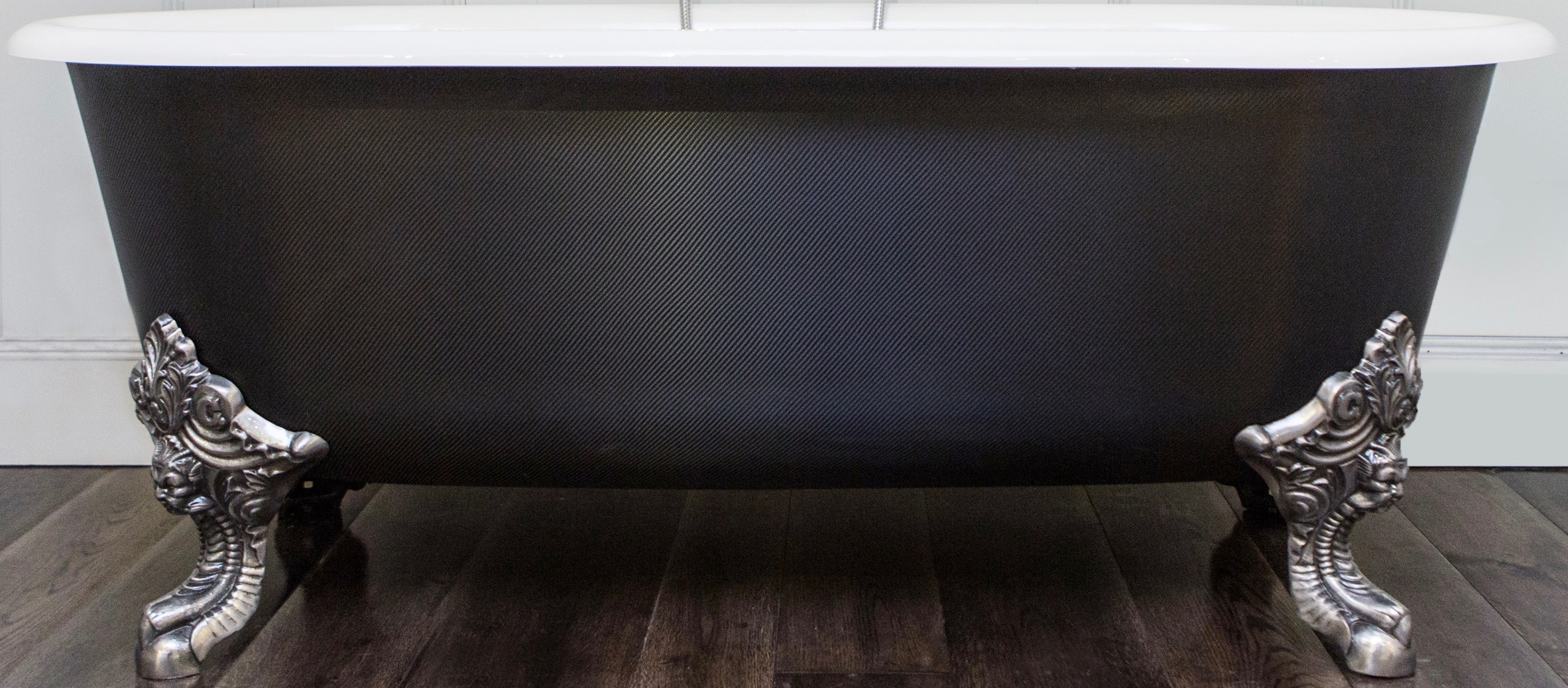 carbon fibre freestanding bath tub with polished metal feet on wooden bathroom floor chadder and co
