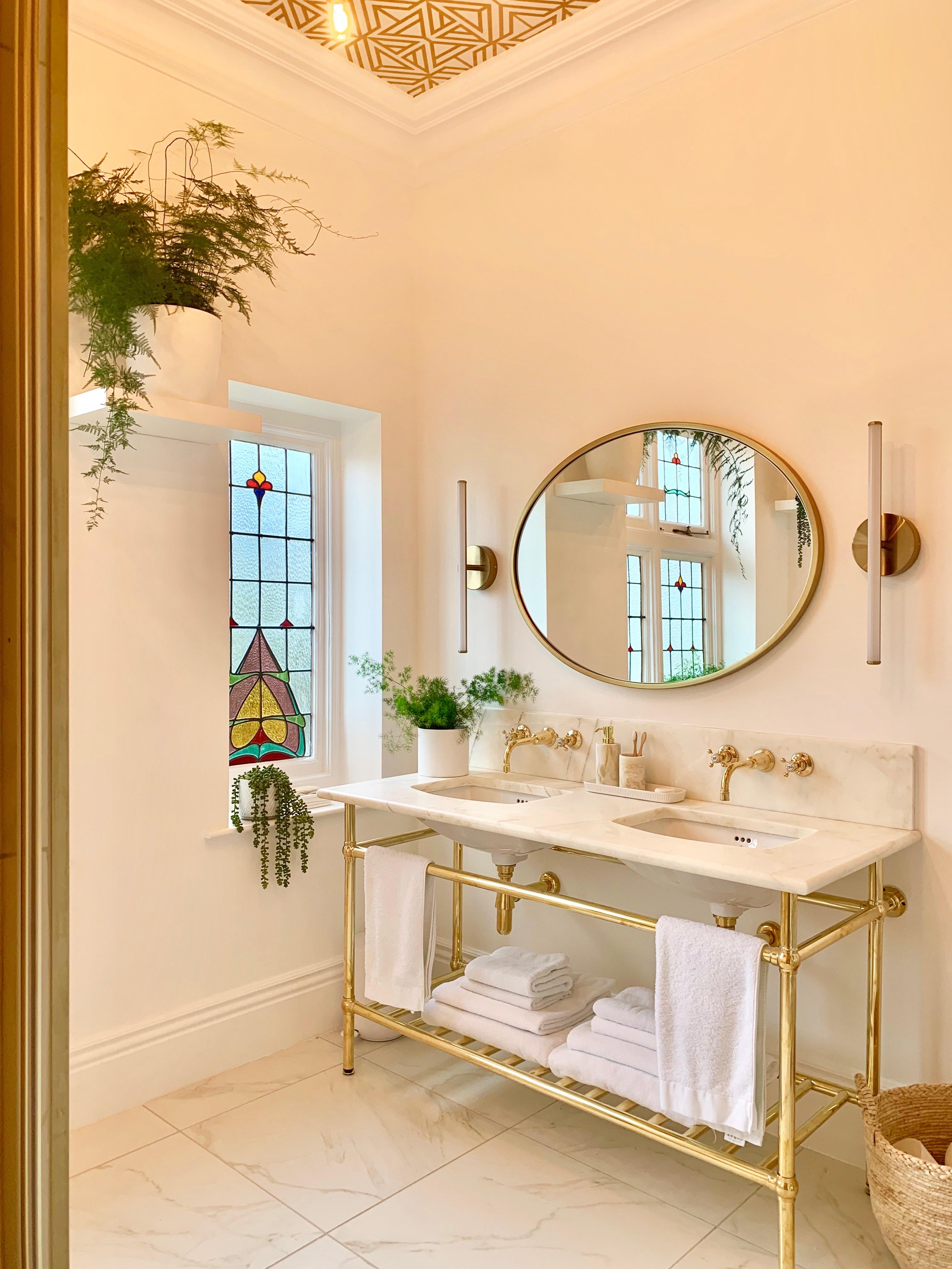 bathroom vanity unit polished brass frame marble floor tiles brass taps faucets